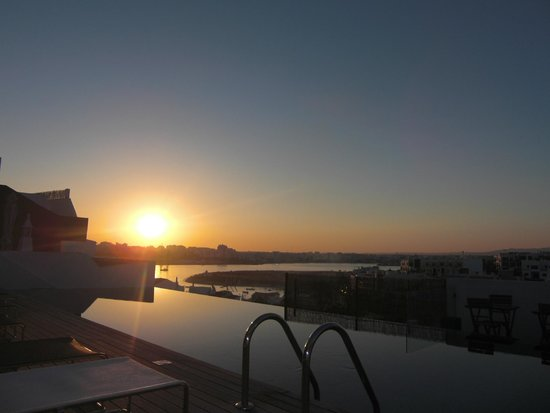 ONE2SEVEN: Zonsondergang vanuit kamer met uitzicht over het zwembad en de haven van het dorpje