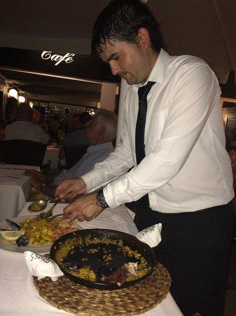 S'Ancora: Le serveur dresse l'assiette juste a coté !!! La paella ... Un délice