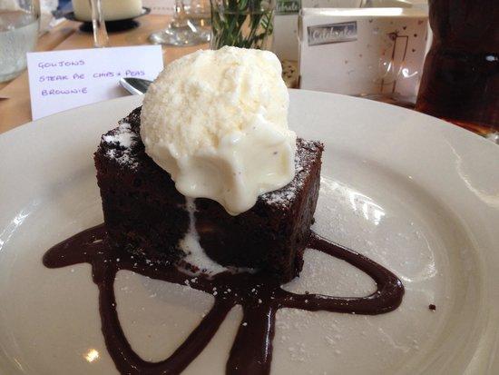 Dark chocolate brownie served with dark chocolate sauce and vanilla ice cream