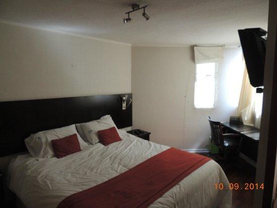 Plaza Suites Apartments: Quarto com mesa e tv.