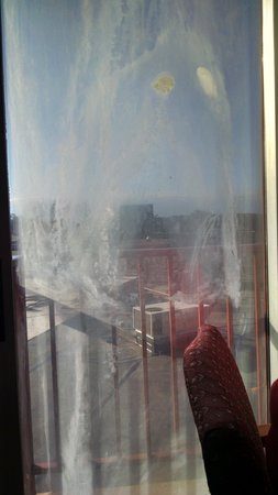 Plaza Hotel and Suites: dirty glass door ...cannot see out to little balcony