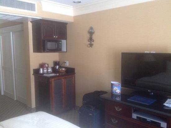 Best Western Plus Sunset Plaza Hotel: microwave, cabinet holding fridge, tv in room 122