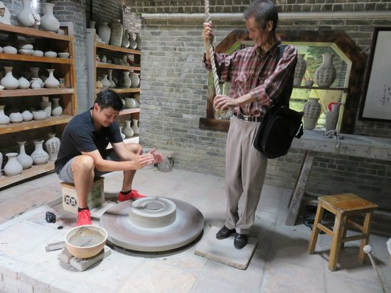 China Connection Tours: Our guide Hobby (plaid shirt) showing us how historic pottery is made.y whe