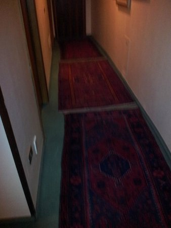 Hotel Carrobbio: Dim lit corridor  (Room 203/8) with worn heavily stained carpets