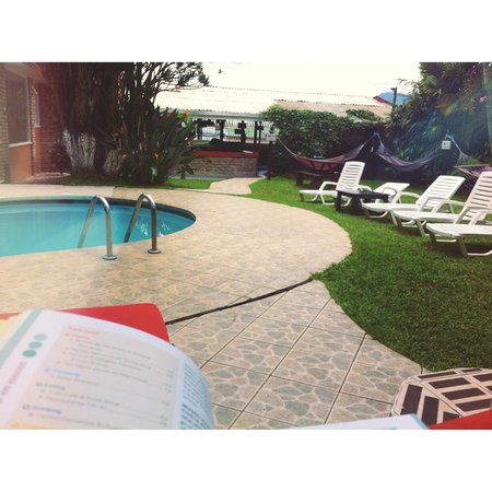 Costa Rica Backpackers: sitting by the pool reading lonely planet