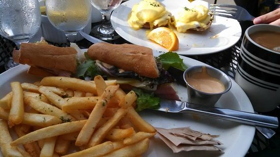 Patisserie Amie: Breakfast sandwhich with ham, brie, apples and a side of fries. Eggs benedict in the background.