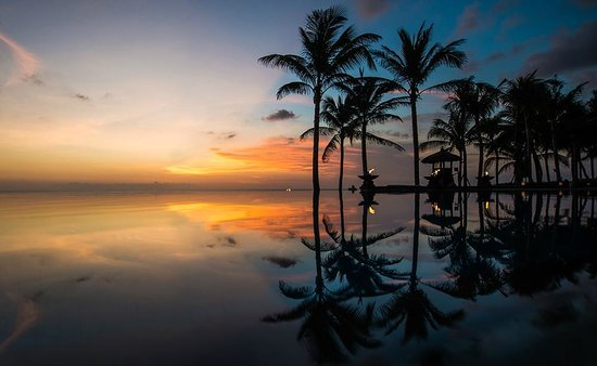 Ocean sunset by the pool -This photo of The Legian Bali is courtesy of TripAdvisor