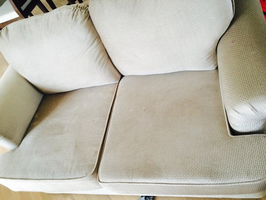 Ambassador Row Hotel Suites by Lanson Place: Worn-out and dusty sofa in a family room