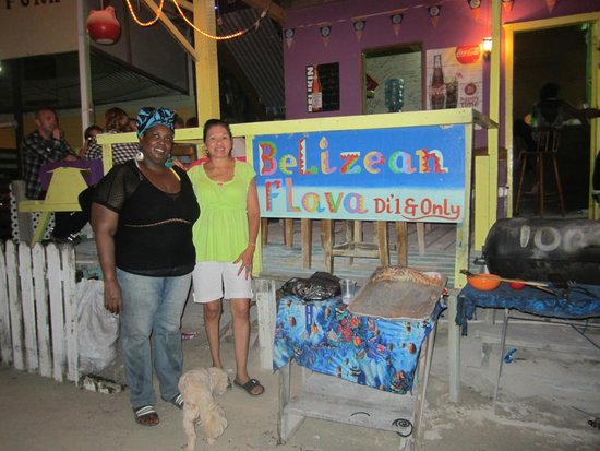 Belizean Flavas : Taking a picture of the colorful sign and owner of the Belizean Flava Restaurant.
