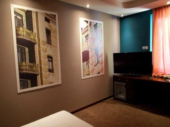 Hotel Cryston: One corner of bedroom with flat panel TV, wall hangings, bed.