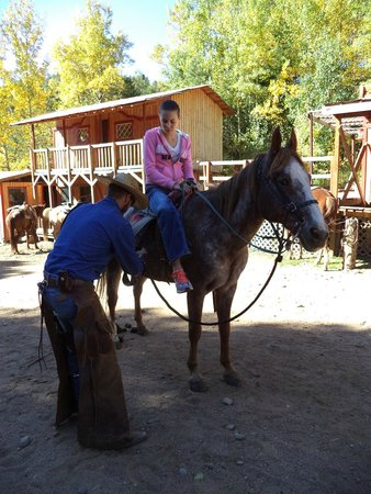 Old Stage Riding Stables: Granddaughter being helped by cowboy.