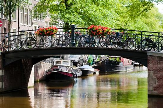 The Netherlands: Bikes parked on an Amsterdam canal.