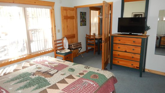 Grand West Village Resort: The bedroom with flat-screen TV, very cute bedspread, and bedside tables. The bathroom is @ the