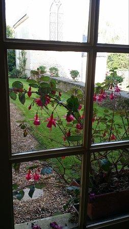 Chateau de la Barre : flowers peeking into the breakfast room with view of chapel in background