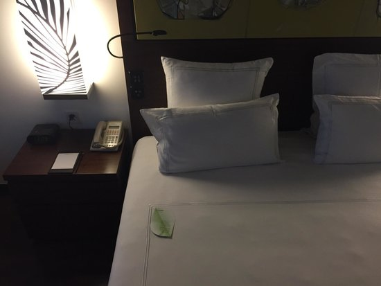 Swissotel Kolkata: Bed linens and bedside table with the digital alarm clock