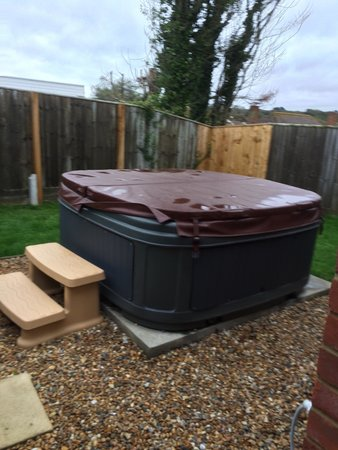 Colwell Bay Holiday Cottages: Garden with hot tub