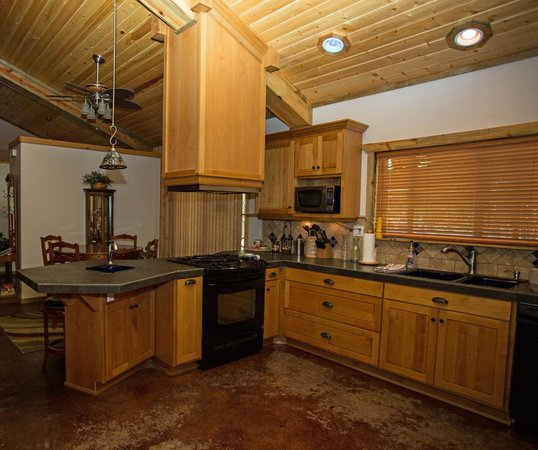 """DiamondStone Guest Lodges: Homestead """"4 Seasons"""" downstairs kitchen with counter top bar and dining area."""