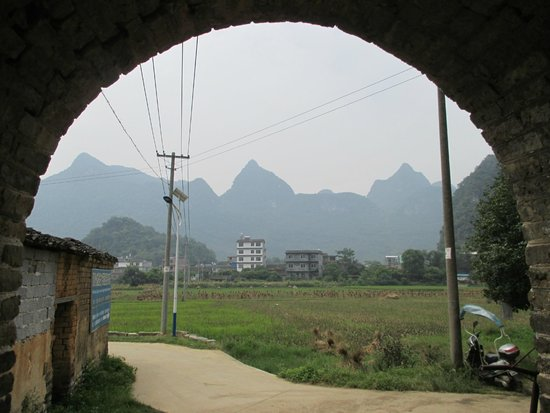 Jiuxian Ancient Village: Looking out from an arched doorway in village Jiuxian accross the fields towards a few peaks