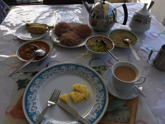 Sam's Guest House: Fish curry for breakfast with fruit, black tea, a coconut thing and some squiggly noodles which