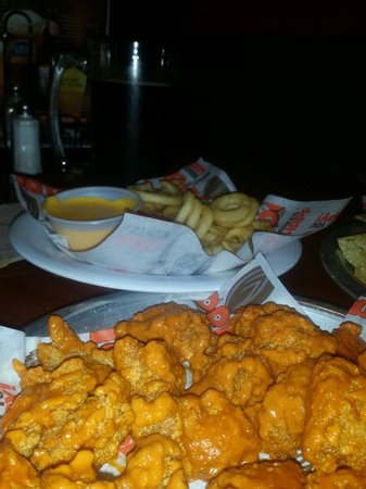 Hooters: Boneless hot buffalo wings, curly fries and chesse sauce. Wings could of been covered in sauce b