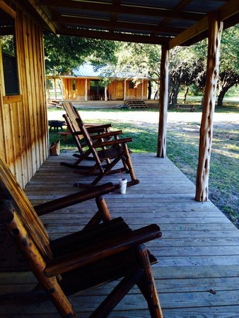 Droptine Ranch: Rocking chairs back porch looking at another cabin