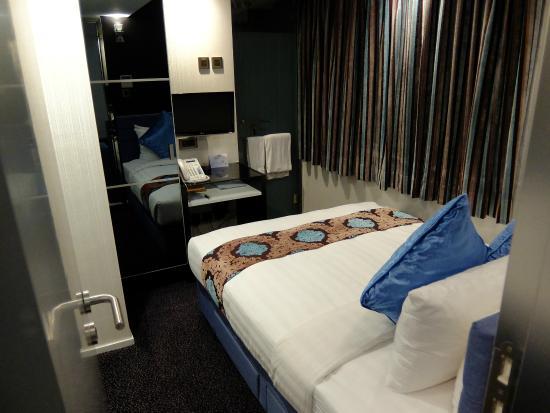 寝室。6畳ほどの広さにクイーンサイズのベッドが占領している ...