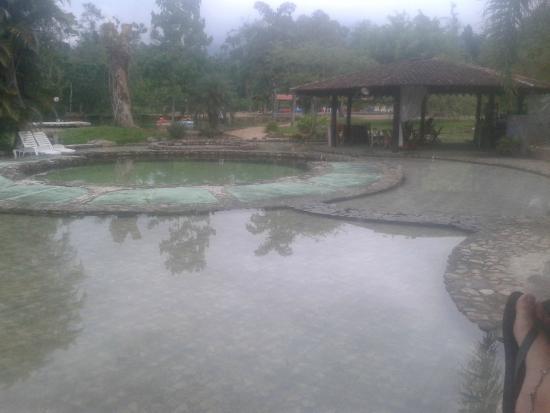 Rancho do Pica Pau Eco Resort: vista da varanda do chalé para piscinas e quiosque/bar