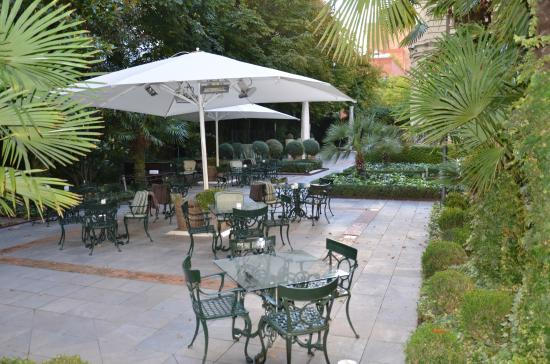 Hotel Santo Mauro, Autograph Collection: Tables and chairs in the garden with heaters under umbrellas