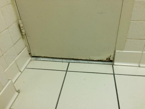 Ramada Sarasota: Rotting bathroom door and rusted hinges.