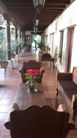 Real Plaza Hotel Suites : Pasillos tipo coloniales con mucha vegetación y sillones para descansar.