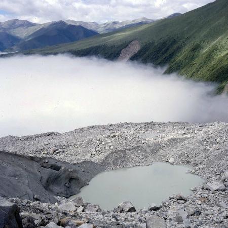 Gongga Temple: Schutt auf Gletscher mit Blick gegen das Kloster (im Talnebel)