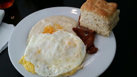 Mama's Boy: Thick cut bacon, cheese grits, eggs & awesome biscuits. Delish raspberry preserves on table.