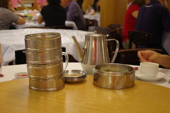 The chinese tea pot with stacked of finished dim sum containers