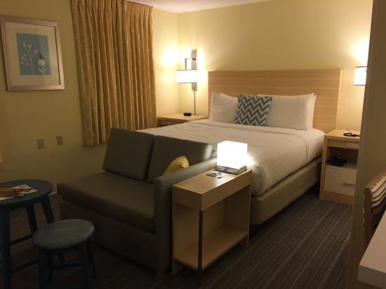 Sonesta ES Suites Houston : Bed and mini modern grey leather couch