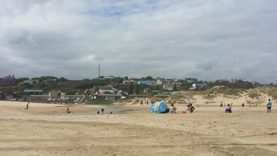 View of the Oyster Inn from the beach. White building on top of the hill with a blue roof