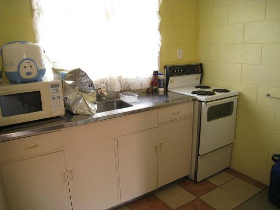 Terume Resort: Kitchen area of studio unit comes with stove, microwave, whiteware and oven.