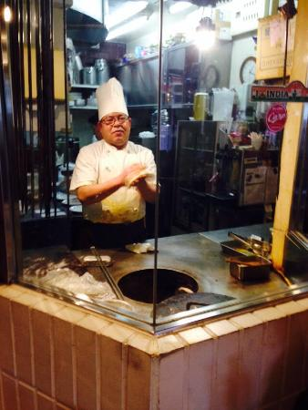 Table-side view of chef making naan at tandoori oven ...