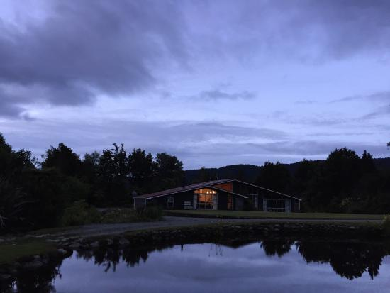 Reflection Lodge: The house in front of a peaceful lake in a evening time.