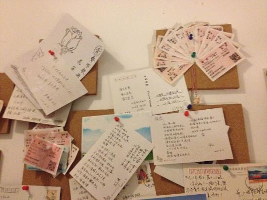 Qing Kong: 壁に貼られた絵はがきやきっぷ