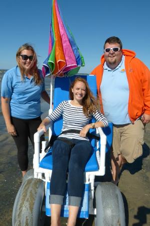 Oasis By The Bay Vacation Resort: Staff with guest using beach wheelchair (provided by Resort)