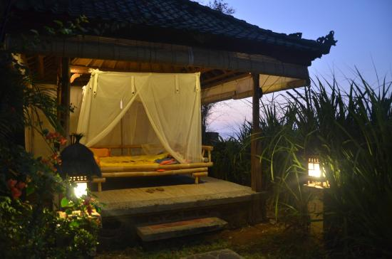 Villa Boreh Beach Resort and Spa Hotel: The daybed for all guests near the pool overlooking the ocean at twilight
