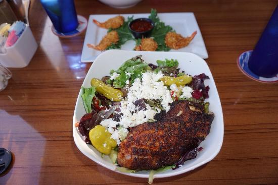 Manatee Island Bar & Grill : Greek salad with blackened grouper, coconut shrimp in the background. Outstanding!