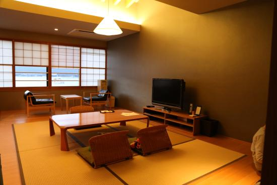 Iroha : tatami style living room with easy chairs by the window and large flat-screen TV