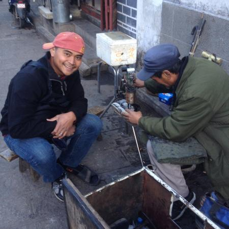 Xizhou Town: Getting my shoes fixed on the corner of Pingdeng Rd and Fuxing Rd