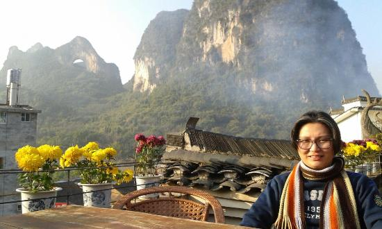 Luna Cafe Yangshuo: The view of Moon Hill from Luna's rooftop - can see smoke from open burning below at the backgro