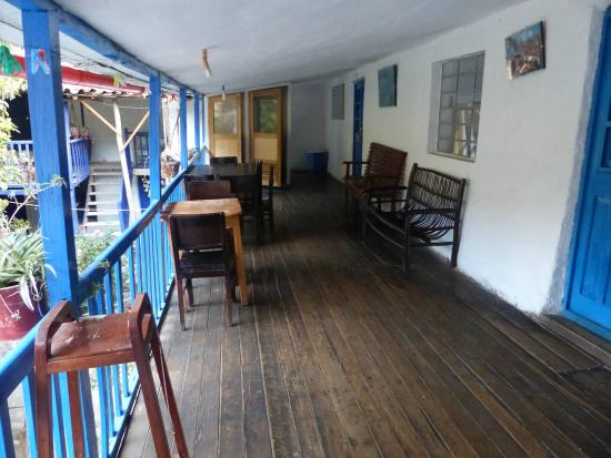 Hostal El Tambo: View of upstairs balcony from far end room.  Half bath at end.
