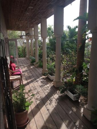 A Stone's Throw Away: Porch area facing pool is a gracious and relaxing spot