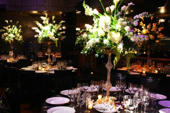 Edison Ballroom: Dramatic grand floral centerpieces adorn tables and purple lighting creates ambiance