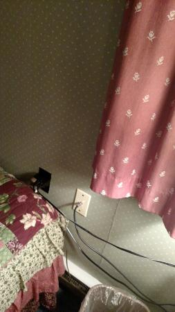 Swiss Inn: Outlet and extension cords next to bed