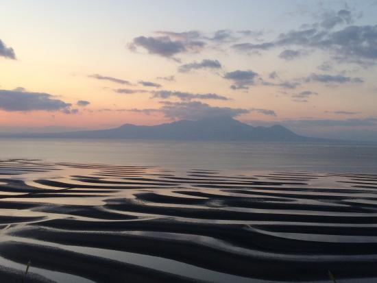 Okoshiki Beach: 普賢岳を背景にした夕焼け時のおこしき海岸